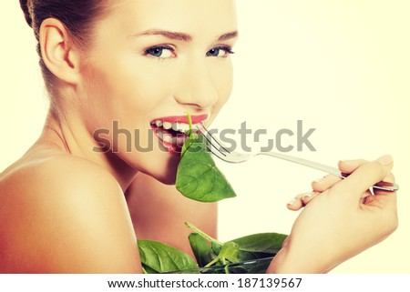 Beautiful caucasian topless woman eating lettuce from a bowl with fork. Isolated on white.
