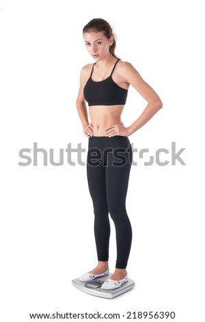 Beautiful caucasian woman checks own weight on scale - stock photo