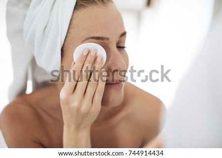 Beautiful Caucasian woman cleaning her face with cotton pad and looking at bathroom mirror.