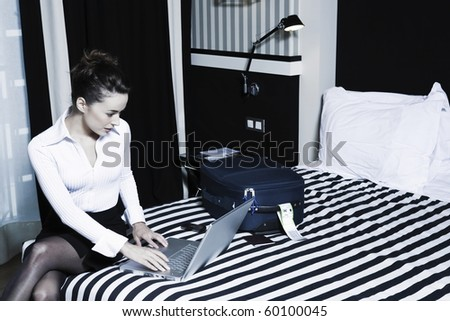beautiful caucasian woman computer typing in a hotel bedroom - stock photo