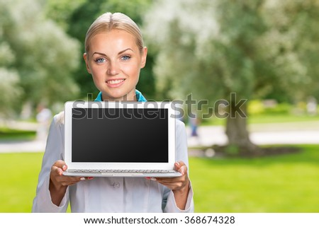 Beautiful Caucasian woman doctor holding a laptop computer  - stock photo