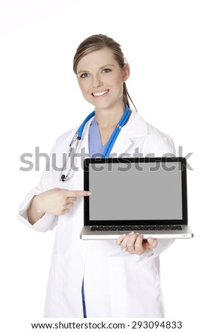 Beautiful Caucasian woman doctor holding a laptop computer and pointing at the screen isolated on a white background.  There is clipping path around the computer screen
