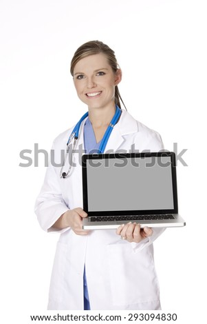Beautiful Caucasian woman doctor or nurse holding a laptop computer with a clipping path around screen. Isolated on a white background - stock photo