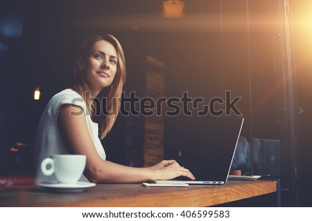 Beautiful Caucasian woman dreaming about something while sitting with portable net-book in modern cafe bar, young charming female freelancer thinking about new ideas during work on laptop computer