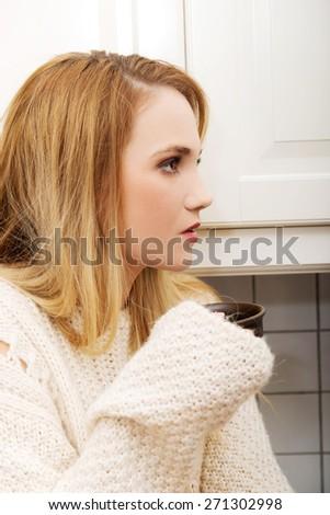 Beautiful caucasian woman drinking coffee in the kitchen. - stock photo