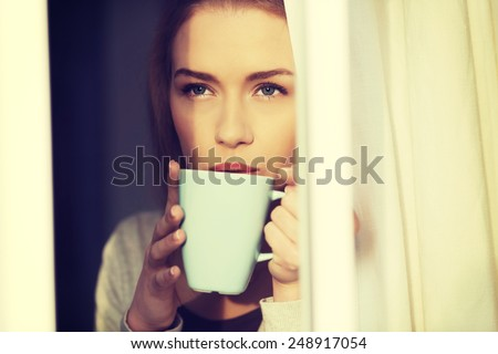 Beautiful caucasian woman drinking hot coffee or tea - stock photo