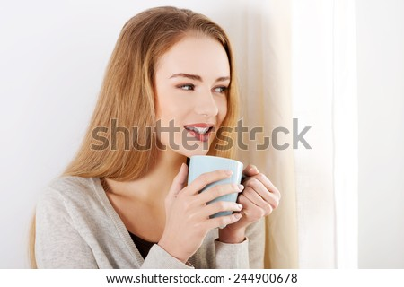 Beautiful caucasian woman drinking hot coffee or tea and looking through window. Indoor background. - stock photo