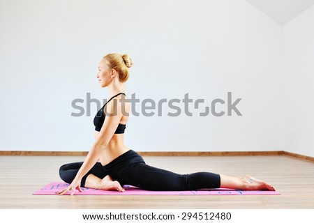 Beautiful caucasian woman exercising yoga indoors  - stock photo