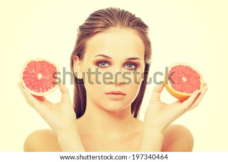 Beautiful caucasian woman holding grapefruit.