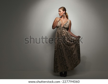 Beautiful caucasian woman in an elegant cocktail dress poses in the studio. Oversized female model on grey background. - stock photo