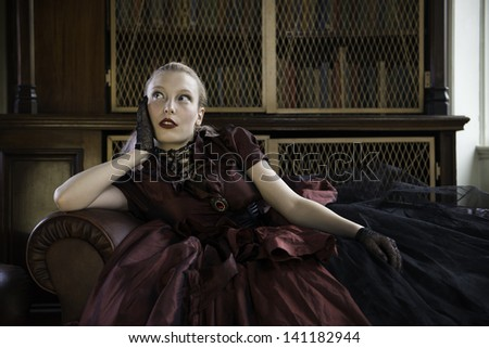 Beautiful Caucasian woman in red Victorian dress lost in thoughts in old library
