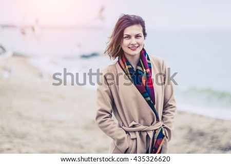 Beautiful Caucasian woman in warm coat enjoying a walking by the beach on the sea background - stock photo