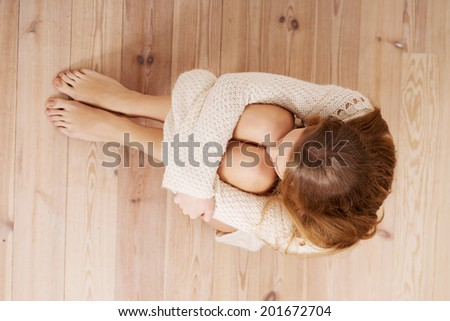 Beautiful caucasian woman is sitting on the floor. Looks as she were hiding from sth. - stock photo