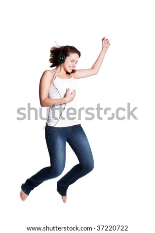 Beautiful caucasian woman jumping for joy  while listening to the music with headphones
