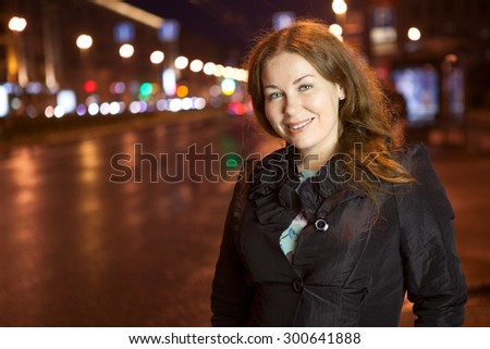 Beautiful Caucasian woman looking at camera while standing on pavement in night city, copyspace - stock photo