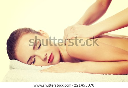 Beautiful caucasian woman lying and relaxing at spa saloon, having massage. Isolated on white. - stock photo