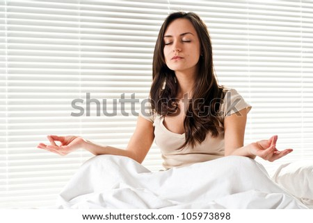 Beautiful Caucasian woman meditating on a bed on a light background