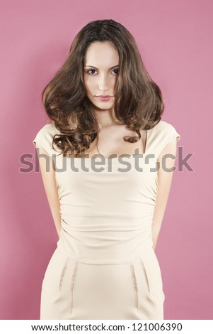 Beautiful caucasian woman model portrait in elegant dress on pink background smiling fresh and happy. - stock photo