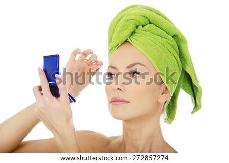 Beautiful caucasian woman plucking her eyebrow. - stock photo