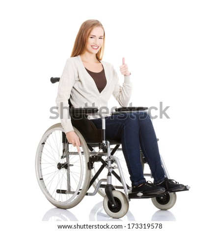 Beautiful caucasian woman sitting on a wheelchair. Isolated on white. - stock photo