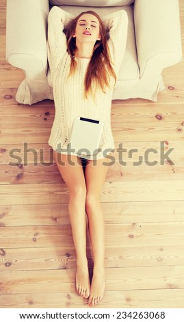 Beautiful caucasian woman sitting on the wooden floor with tablet. - stock photo