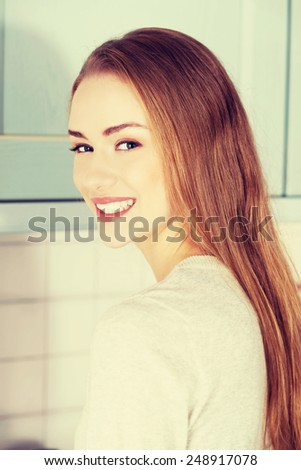 Beautiful caucasian woman standing in the kitchen. - stock photo