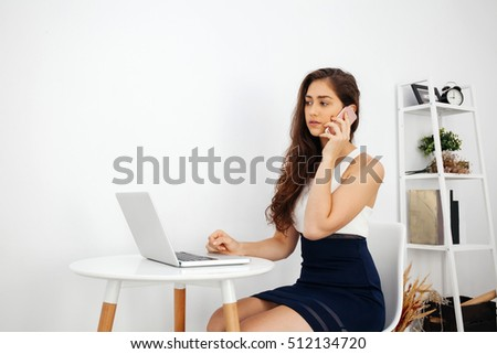 Beautiful Caucasian woman talking on the phone while using laptop on white desk over clean home office with copy space