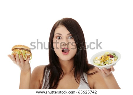 Beautiful caucasian woman thinking whot to eat: hamburger or salat. Isolated on white - stock photo
