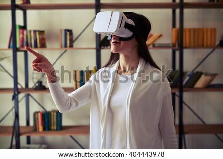 Beautiful Caucasian woman touch something using modern virtual reality glasses - stock photo
