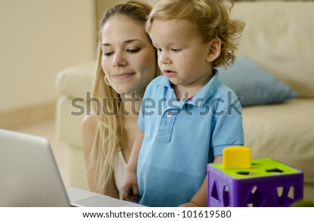 Beautiful caucasian woman using a laptop with her son