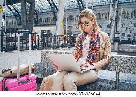 Beautiful Caucasian woman using net-book while sitting in train station interior. modern businesswoman using a laptop computer while waiting for the train - stock photo