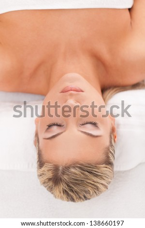 Beautiful caucasian woman with blond hair lying in a spa