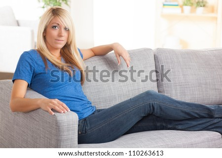 Beautiful Caucasian woman with blond hair relaxing on couch in living room wearing a blue shirt and jeans.