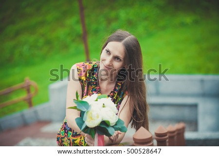 beautiful Caucasian woman with flowers in nature .