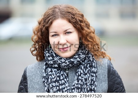 Beautiful Caucasian woman with long curly hair, head and shoulders portrait - stock photo