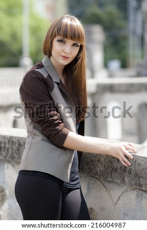 Beautiful, caucasian, young, long haired, brown eyed woman posing in urban locations with natural background