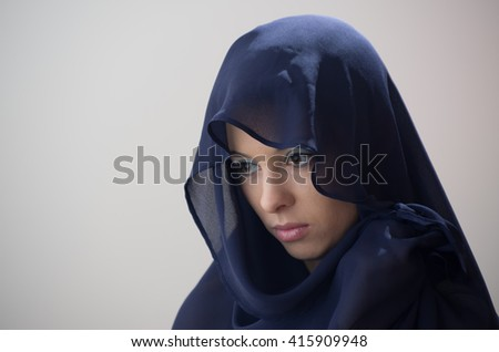 Beautiful caucasian young mysterious woman in blue veil.