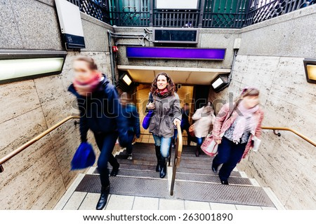 Beautiful caucasian young woman at tube exit in London with blurred people around on the stairs. She is looking up and wearing winter clothes. - stock photo