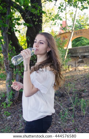 Beautiful caucasian young woman drinking a bottle of mineral water in the nature after fitness exercise