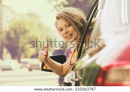 Beautiful caucasian young woman in car showing the thumb up