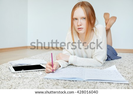 Beautiful Caucasian young woman with red hair and blue eyes looking at the camera with serious and concentrated expression while getting ready with homework composition after classes at university  - stock photo