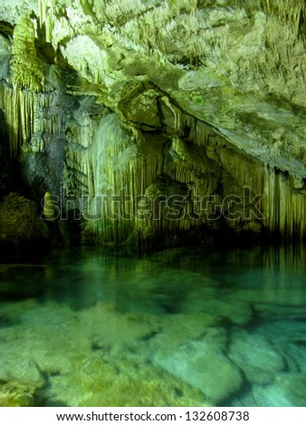 Beautiful cave interior with reflections in clear underground water and lighting - stock photo