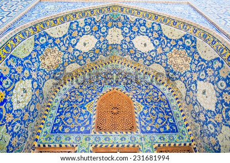 Beautiful ceramic tile with Persian patterns in the niche with wooden window of a historic building in Isfahan, Iran - stock photo