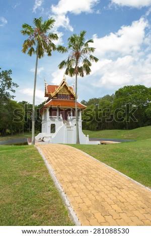 Beautiful chapel of Buddha at middle pool and green grass all around - stock photo