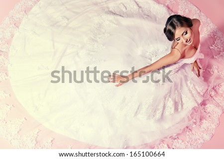 Beautiful charming bride in a luxurious dress looking up. Over pink background. - stock photo