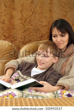 Beautiful charming Caucasian mother with her son reading a book on a brown background