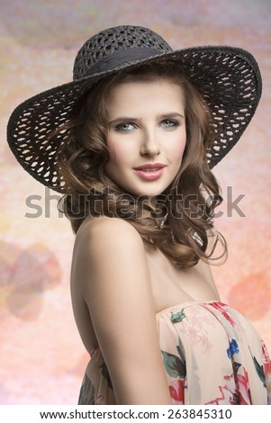 Beautiful, charming, cheerful, brunette girl with colorful make up. She is wearing summer hat and delicate top with floral pattern. - stock photo