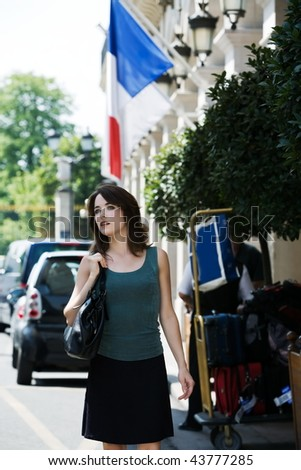 beautiful charming woman at the exit of a hotel with her luggage - stock photo