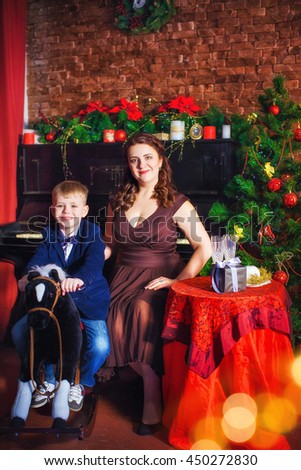 Beautiful charming woman mother sitting at the table, son sitting on toy horse on the background of Christmas trees, black piano. Closeup, Macro, Background - stock photo