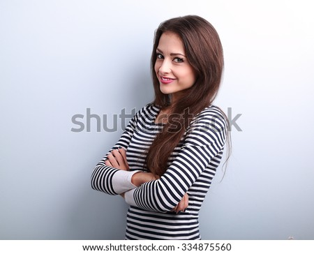 Beautiful charming young casual woman with folded hands looking happy on blue background with empty copy space